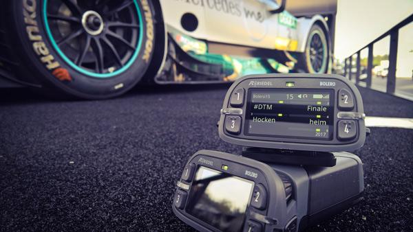 Uno de los sistemas de intercom Bolero de Riedel en el suelo de una pista de carreras junto a un coche