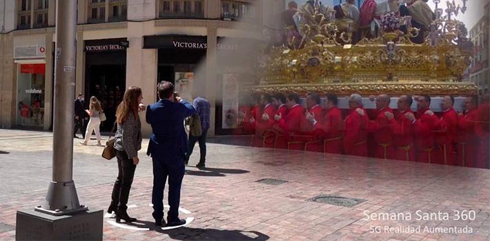 """Telefónica está trabajando en un programa piloto junto al Ayuntamiento de Málaga, donde el 5G y la realidad aumentada aportarán un nuevo enfoque al turismo de la ciudad. En este caso, se trata de una aplicación, que trasladará al usuario a la Semana Santa del año 2019. Hace dos años, usando la tecnología de cámaras 360, se grabaron loas principales procesiones que recorren la capital malagueña. Gracias a esas filmaciones, ahora nos podemos trasladar a los tiempos pre pandemia. De este modo, a través de una aplicación instalada en teléfonos y Tablet 5G, los usuarios podrán vivir el recorrido de las procesiones ubicándose en diferentes puntos del centro histórico de la ciudad, como la Calle Larios o el Puerto de Málaga. Una vez ubicados, vivirán una experiencia inmersiva, en la que podrán ver y oír los sonidos de aquel momento en cualquier época del año. En este proyecto piloto Telefónica ha trabajado con VRESTUDIO y Vector Pipe SL, dos empresas locales malagueñas situadas en el Polo Nacional de Contenidos Digitales de la ciudad y punteras en realidad virtual, aumentada y en la distribución de video. Tal y como indica Mercedes Fernández, gerente de Innovación de Telefónica España: """"el turismo es un sector con gran potencial para el 5G de cara a proporcionar a los usuarios nuevas formas de visitar y descubrir diversos destinos y festividades con experiencias más reales e inmersivas. La posibilidad de ver la Semana Santa que hoy presentamos vendría a completar otros pilotos puestos en marcha en Segovia y en Barcelona que permiten al visitante verse inmerso en escenas de siglos pasados en escenarios reales del presente o superponer información relevante de lo que estamos viendo mientras vamos en un autobús turístico""""."""